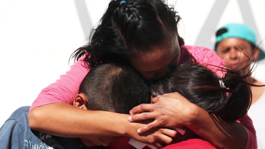 Una mujer abraza a unos niños en el escenario de la tragedia en México tras la explosión durante la toma de combustible de un ducto