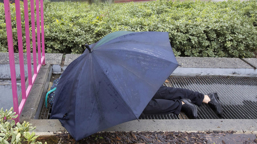 Un hombre duerme sobre una rejilla de aire caliente en Los Ángeles el pasado jueves para combatir las bajas temperaturas de la tormenta Harper.