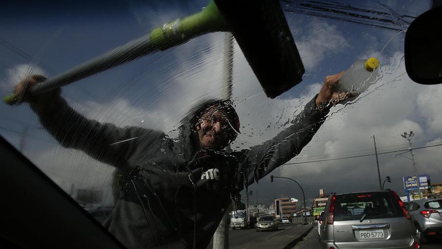Un migrante venezolano limpia los cristales delnateros de un carro en Quito, la capital de Ecuador.