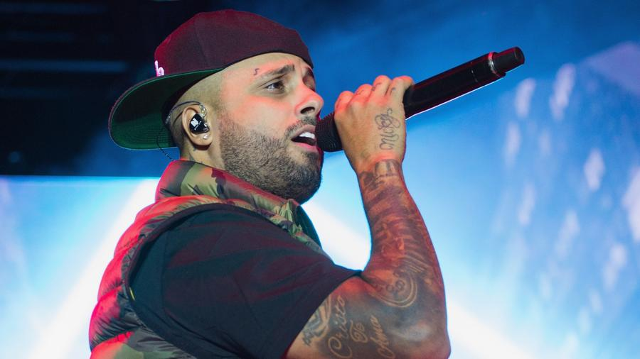 Nicky Jam wears backwards cap during concert.