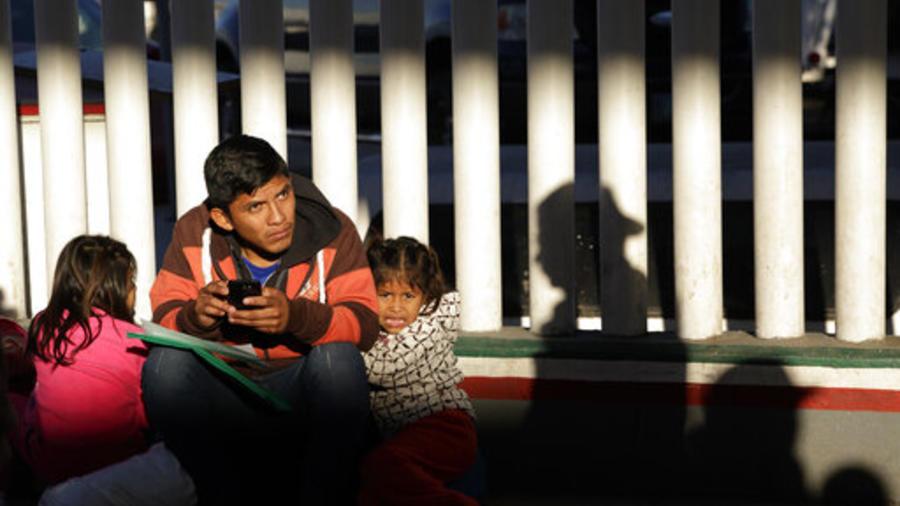 Un migrante y sus hijas esperan su turno en Tijuana, México, para presentar una solicitud de asilo en Estados Unidos.