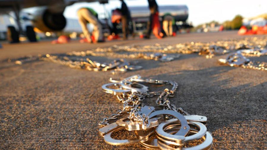 Varias esposas permanecen en el suelo mientras que se prepara un vuelo para deportar a cientos de inmigrantes que ingresaron al país de manera ilegal.