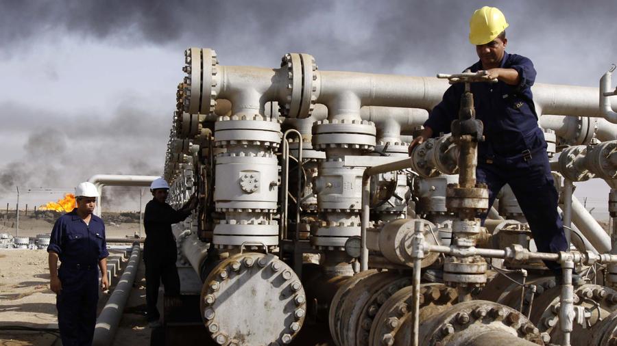 obreros iraquíes trabajando en la refinería de Rumaila