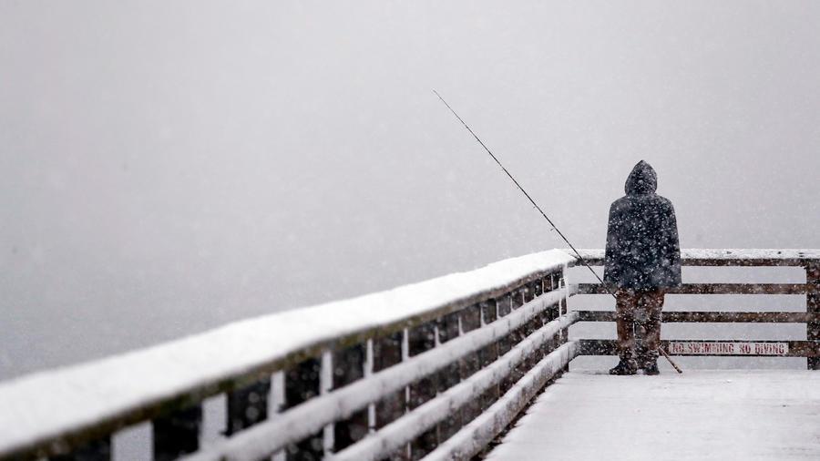 Un hombre en un muelle en el estado de Seattle en mitad de la nieve