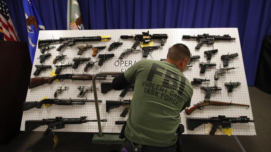 Un agente del FBI frente a armas decomisadas en la operación en Los Ángeles este miércoles.