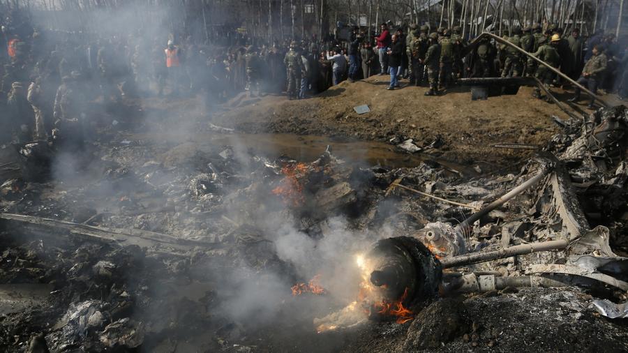 Aldeanos de Cachemira y soldados del ejército indio se reúnen cerca de los restos de un helicóptero indio