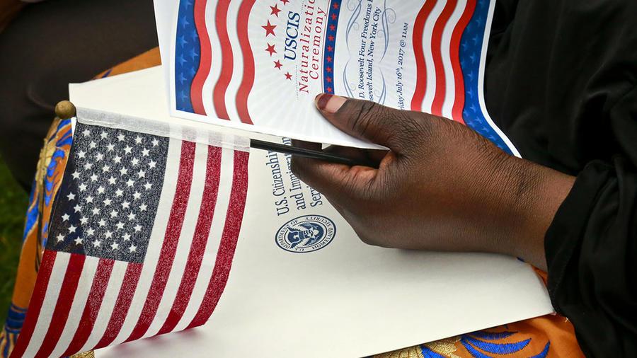 Una persona sostiene un programa y la bandera estadounidense durante una ceremonia de naturalización.