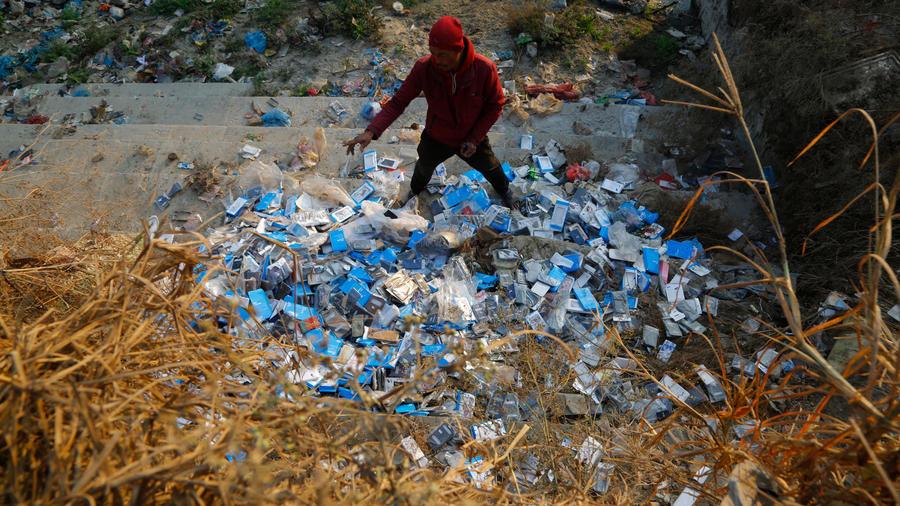 Un hombre sobre un montón de botellas de agua de plástico