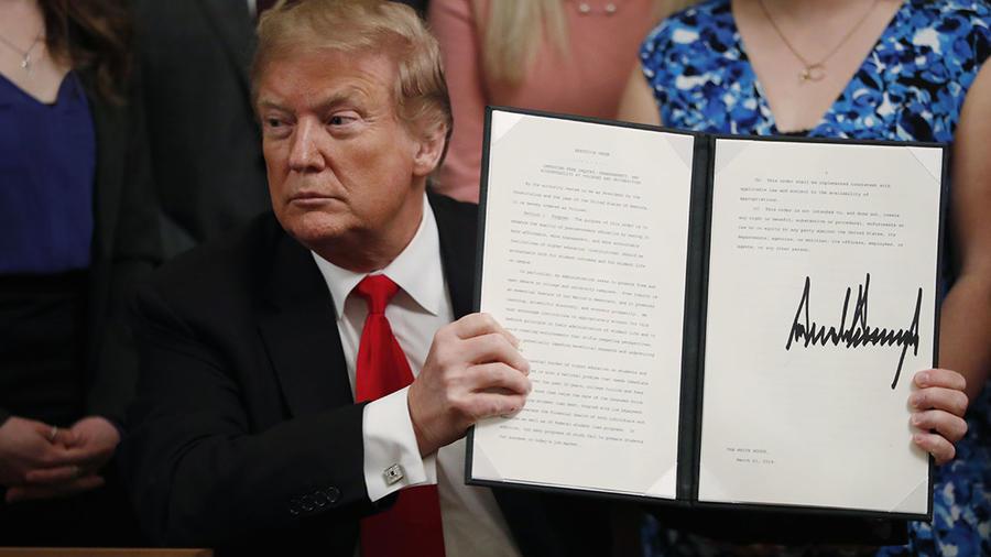 El presidente Donald Trump sostiene una orden ejecutiva en la que obliga a las universidades a apoyar el libre discurso.
