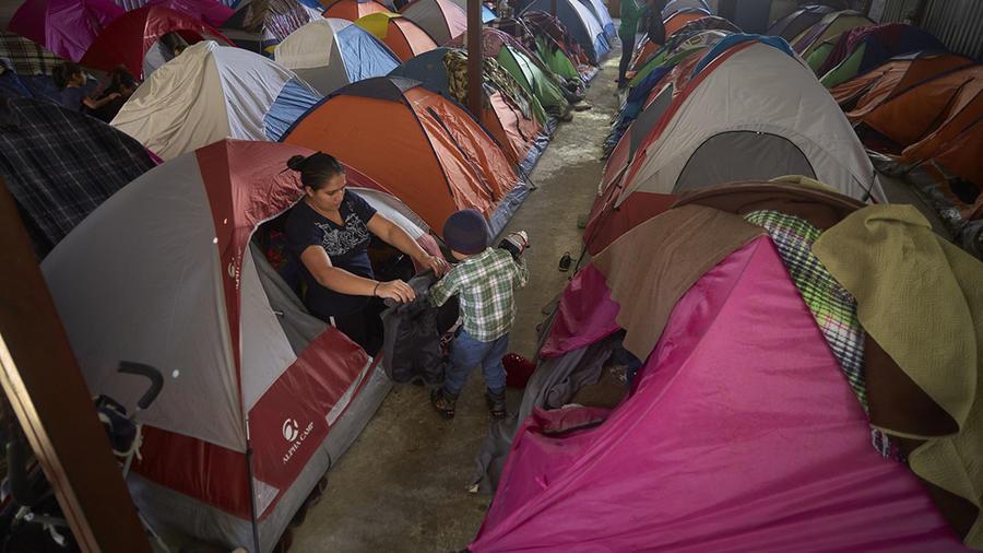Una madre ayuda a su hijo a vestirse en uno de los albergues para migrantes en Tijuana, México.