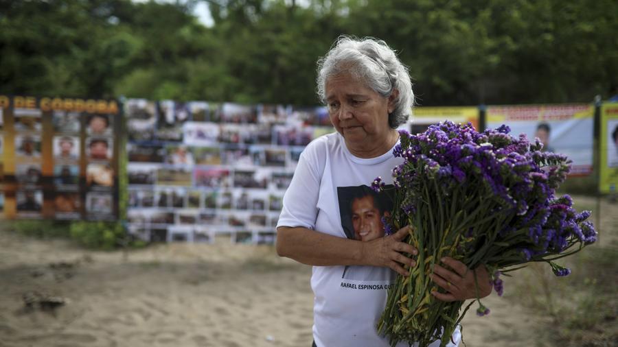 Una mujer que busca a un familiar desaparecido lleva flores en un sitio donde hallaron 300 restos humanos en México