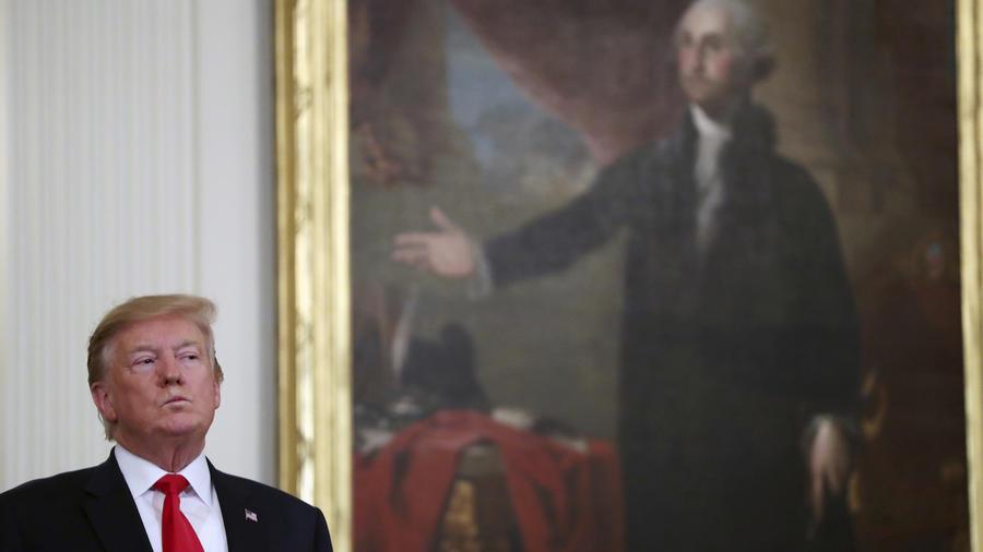 Trump, este viernes en un acto en la Casa Blanca, junto a un retrato del presidente George Washington.