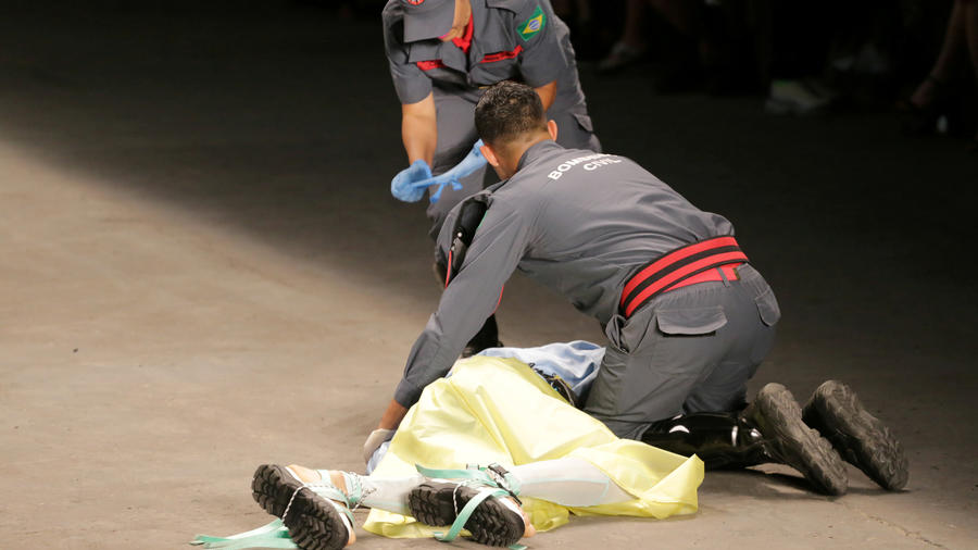 Dos socorristas ayudan al modelo brasileño Tales Cotta tras desplomarse en la pasarela de la Semana de la Moda en Brasil.