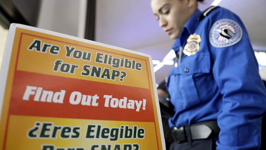 Una empleada de la Administración de Seguridad del Transporte es captada al lado de un anuncio sobre cómo obtener ayuda pública del gobierno.
