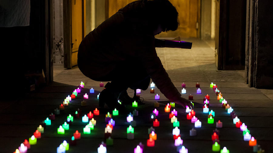 Una mujer enciende unas velas en medio de un cuarto totalmente oscuro.