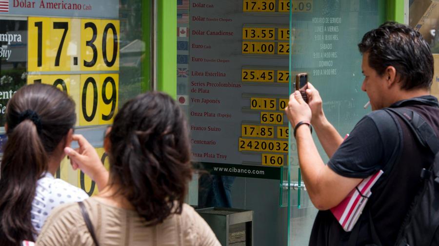 Varias personas miran la cotización del peso mexicano en una imagen de archivo