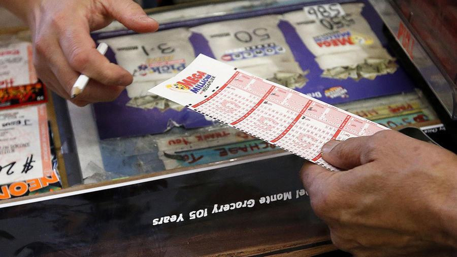 Una persona entrega en un supermercado los números que escogió para jugar en el Mega Millions de la lotería.