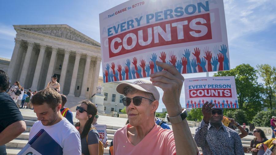 """Activistas pro-inmigración en una manifestación en Washington DC en abril de 2019 sosteniendo pancartas que dicen """"cada persona cuenta""""."""