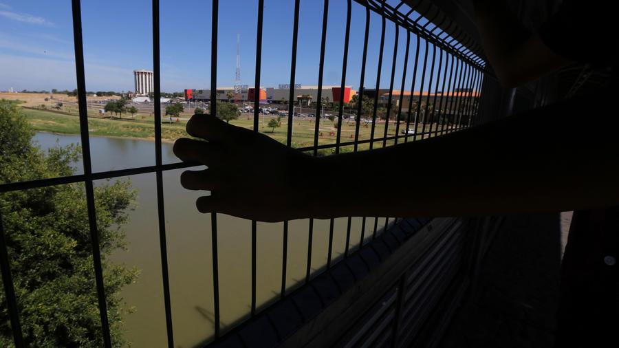 Un solicitante de asilo con una mano sobre reja en la frontera entre México y EEUU