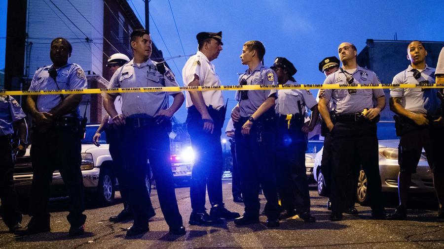 Policías hacen guardia alrededor del perímetro donde se desató una balacera en un vecindario de Philadelphia