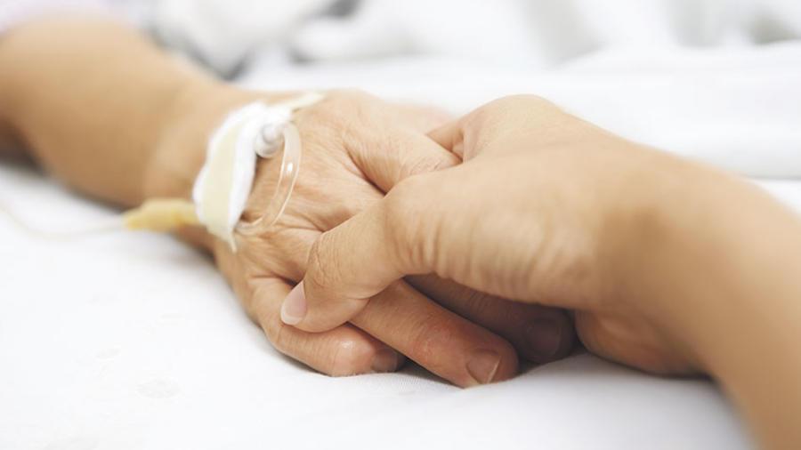Una persona sujeta la meno de un enfermo