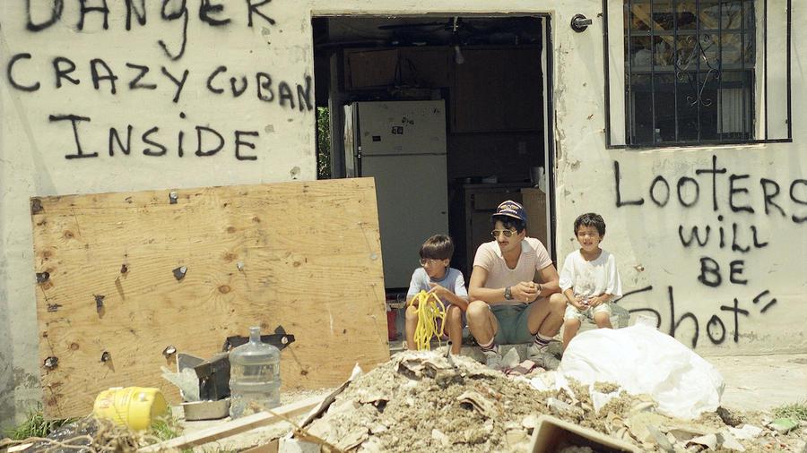 """Orlando Somante, sentado el 27 de agosto de 1992 con sus hijos a la entrada de su casa en Cutler Ridge. En la pared, dos mensaje: """"Se disparará a los ladrones"""", y """"Peligroso cubano loco dentro""""."""