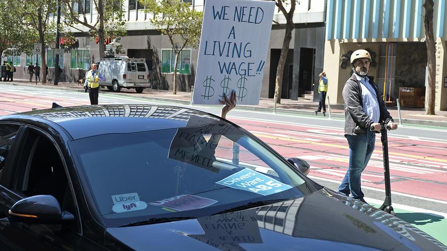 Un chofer de Uber y Lyft sostiene un cartel de protesta por los salarios en San Francisco, California.