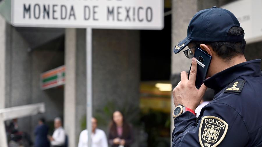 Un policía habla por teléfono afuera de la Casa de la Moneda en la ciudad de México