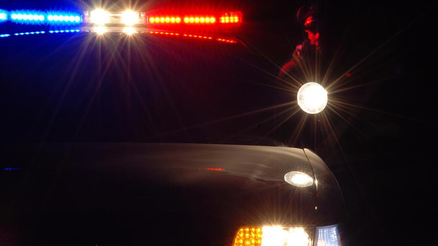 Un policía apunta con su arma y linterna detrás de una patrulla.