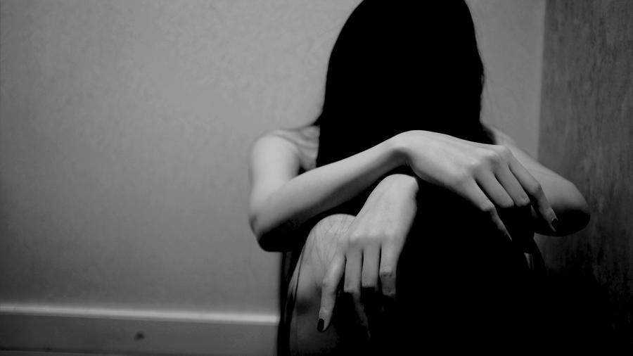Una mujer permanece sentada y cabizbaja en la esquina de una habitación oscura.