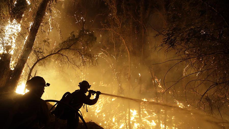 Bomberos tratan de contener las llamas del incendio María, en Somis, California.