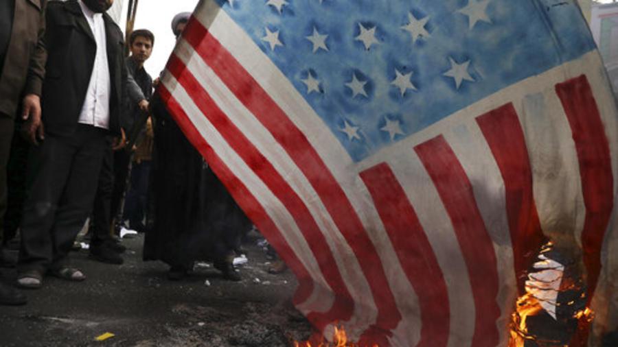Manifestantes queman este lunes una reproducción de una bandera de EEUU durante la conmemoración de la toma de la embajada estadounidense en Teheran.