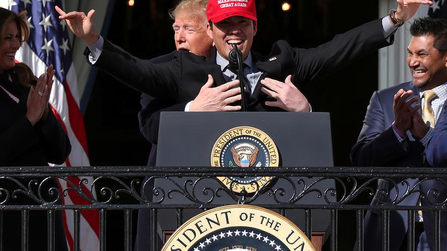 Trump abraza al receptor Kurt Suzuki en el recibimiento de los campeones de la Serie Mundial de la Liga Mundial de Béisbol, los Washington Nationals, en la Casa Blanca.