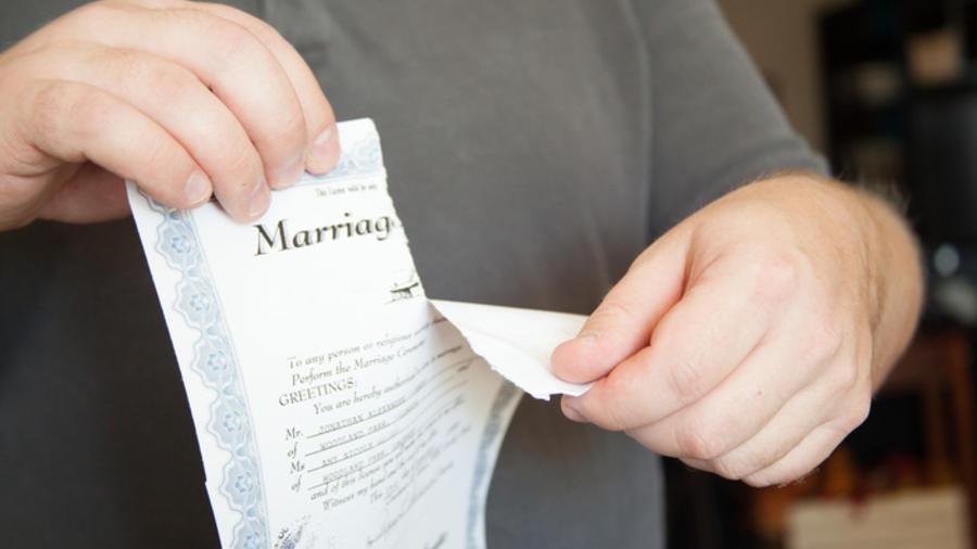 Un hombre rompiendo un certificado de matrimonio por la mitad.