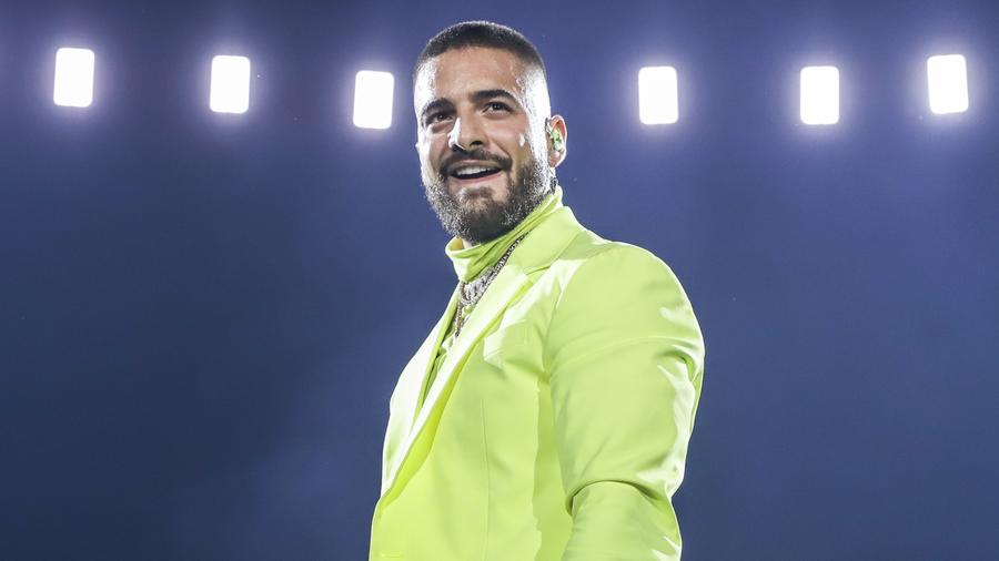 Maluma wearing a neon outfit during live show.