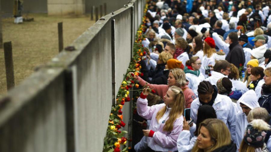 Personas dejan flores cerca de una de las partes que quedan del muro de Berlín, cuya caída ocurrió hace treinta años.