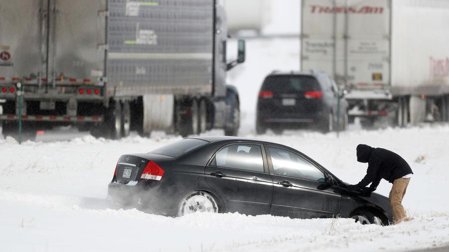 Un hombre con su vehículo varado en la nieve en Colorado