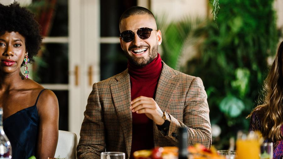 Maluma wearing turtle neck and smiling at camera