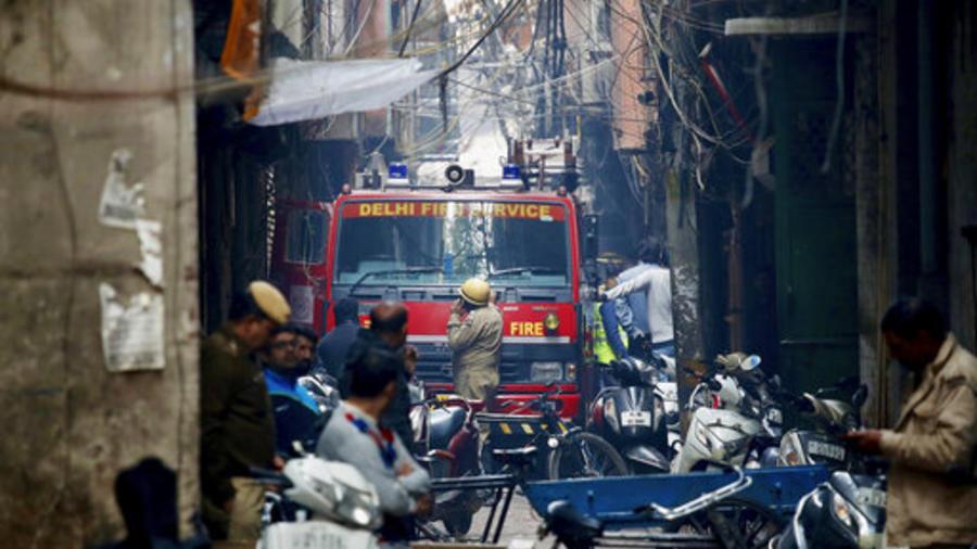 Un camión de bomberos se encuentra junto al lugar de un incendio en un callejón, enredado en cables eléctricos y demasiado estrecho para que los vehículos puedan acceder, en Nueva Delhi, India, el domingo 8 de diciembre de 2019.
