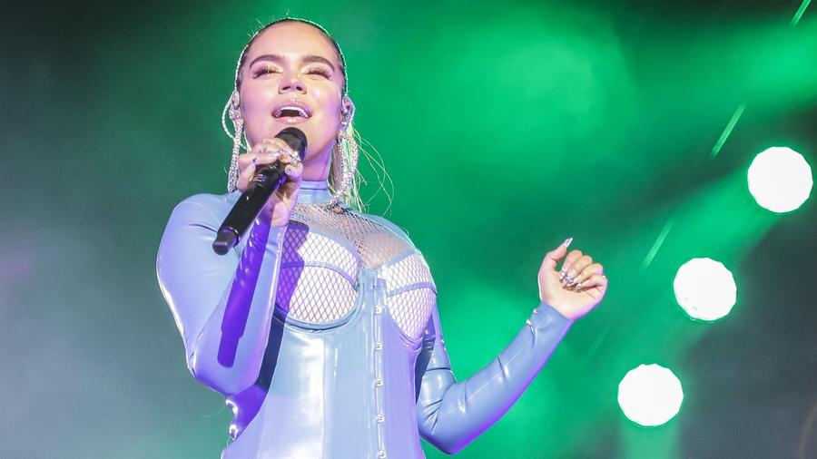Karol G in concert wearing blue leather outfit