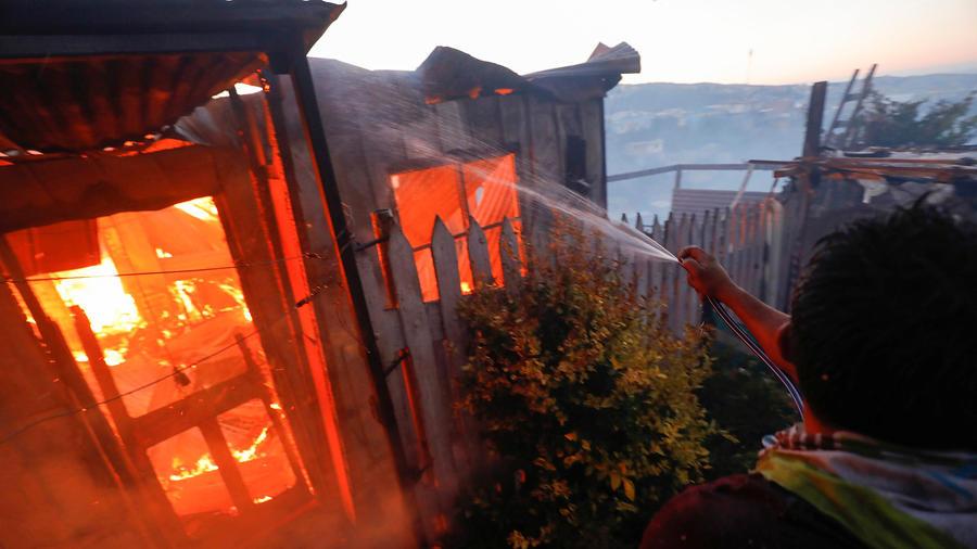 Una persona intenta apagar las llamas que incendian su hogar en Valparaíso.