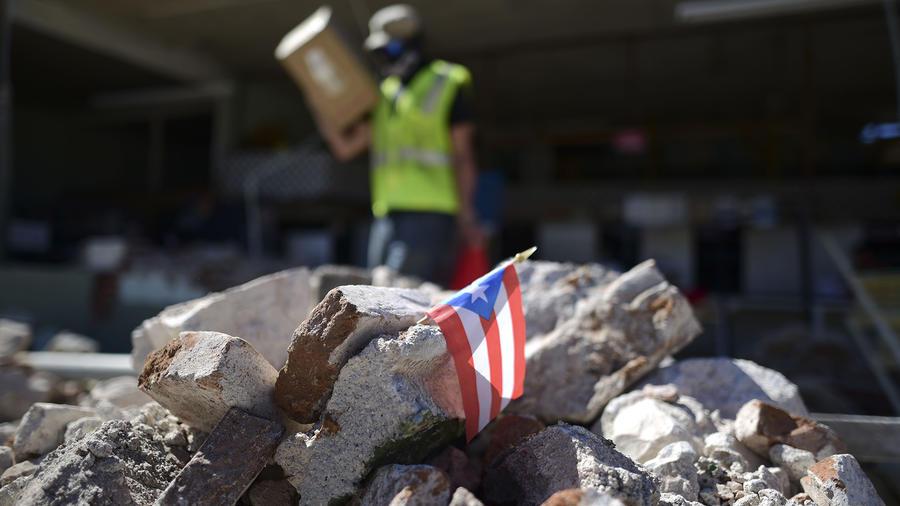 Una bandera de Puerto Rico entre los escombros que dejó el terremto.