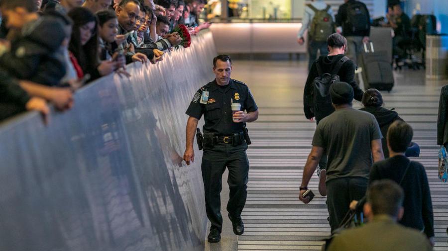 Un oficial del aeropuerto pasa junto a viajeros internacionales que llegan al Aeropuerto Internacional de Los Ángeles en el primer día de exámenes de salud para el coronavirus de personas que vienen de Wuhan, China