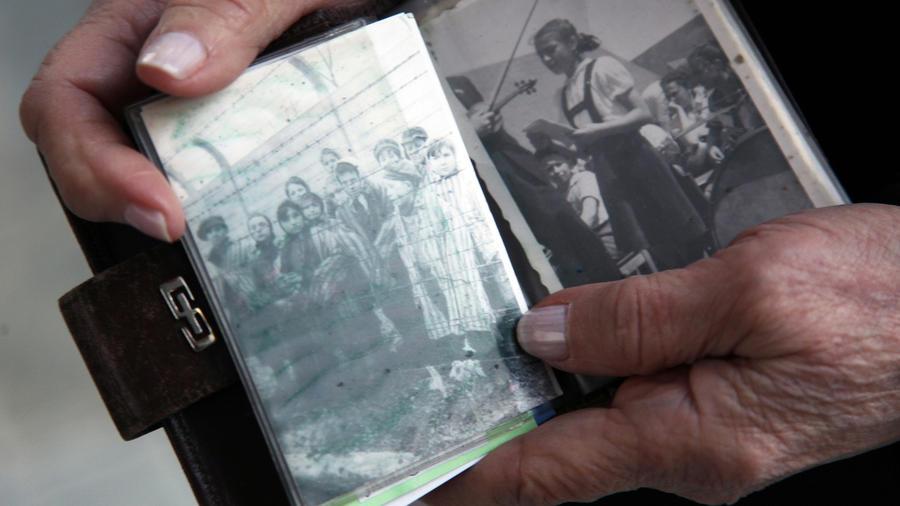 Una sobreviviente de Auschwitz muestra una foto de cuando era prisionera.