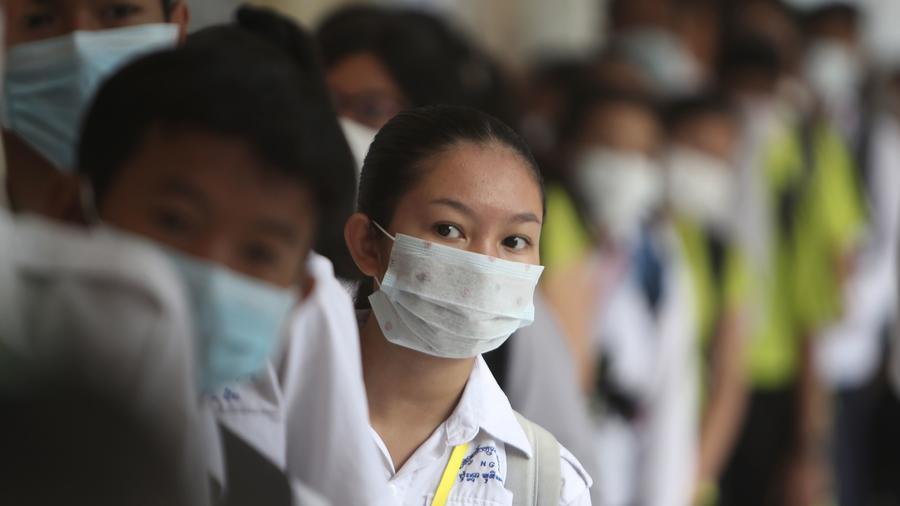 Estudiantes en Camboya hacen una fila para desinfectar sus manos