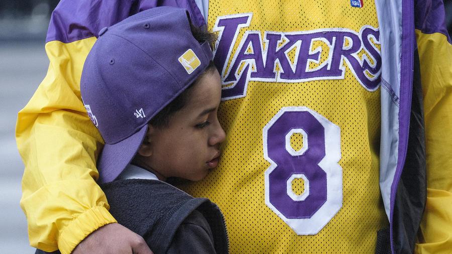 Un niño y su padre en el memorial por las víctimas del accidente aéreo en Staples Center, Los Angeles.