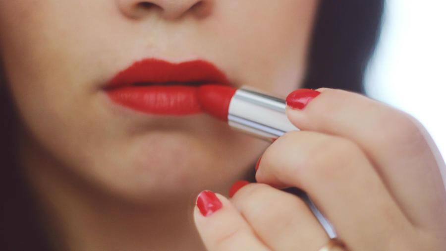 Mujer aplicando lipstick rojo