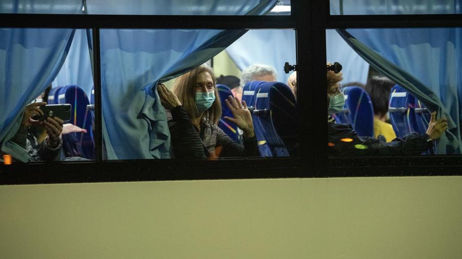 Ciudadanos estadounidenses saludan desde un autobús mientras abandonan el crucero Diamond Princess para ser repatriados.