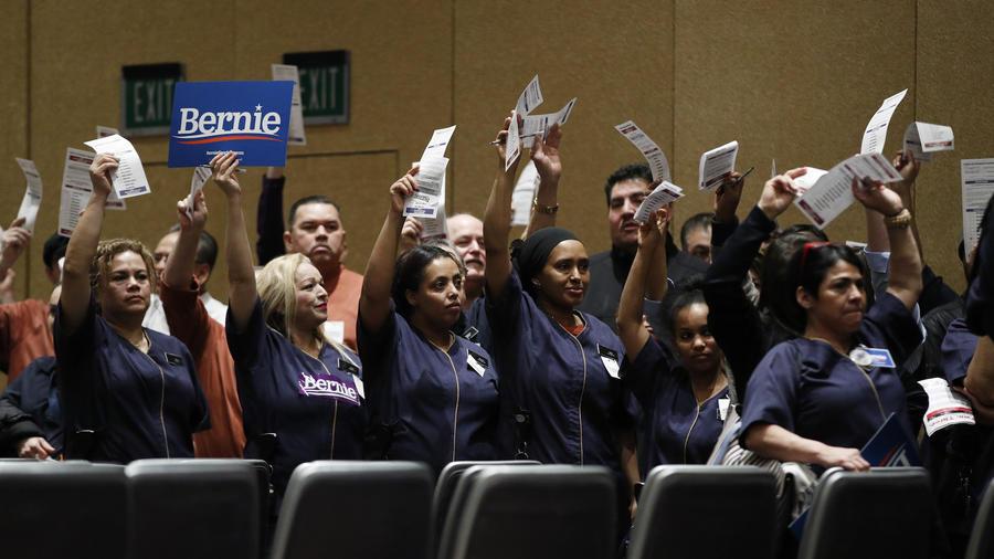Trabajadores de un casino de Las Vegas levantan sus tarjetas de votación en favor de Sanders este sábado en el caucus demócrata.