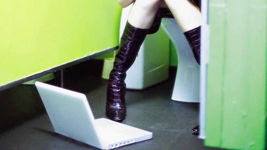 Mujer en baño con computadora encendida